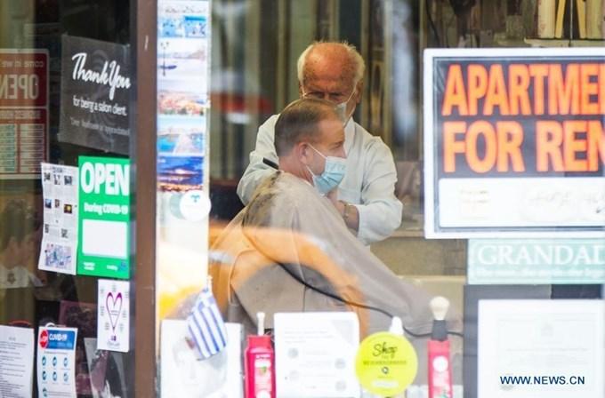 Thợ cắt tóc và khách hàng đeo khẩu trang phòng COVID-19 tại Toronto, Cananda, ngày 16/11. (Ảnh: Xinhua)