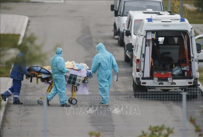 Nhân viên y tế chuyển bệnh nhân mắc COVID-19 tới bệnh viện ở ngoại ô Moskva, Nga. Ảnh: THX/TTXVN
