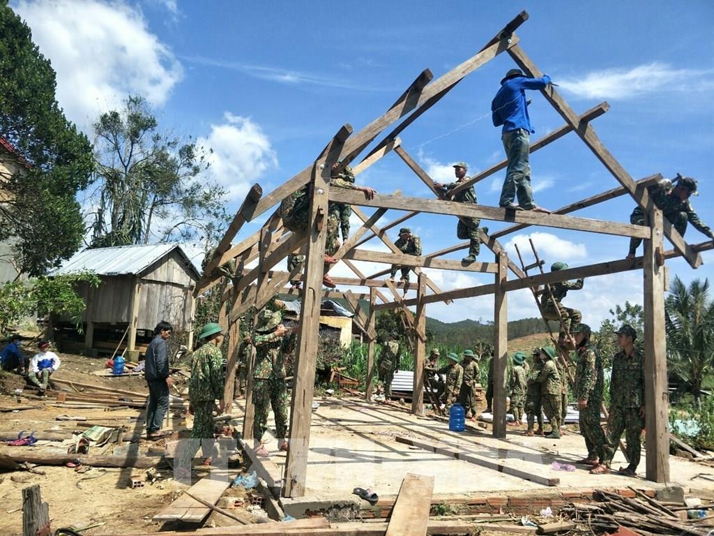 Cán bộ, chiến sĩ giúp dân dựng lại nhà cửa sau bão số 9 tại tỉnh Gia Lai. Ảnh: TTXVN