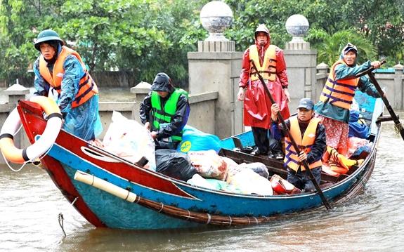 Dân quân huyện Lệ Thủy (Quảng Bình) dùng thuyền đánh cá cứu giúp dân trong lũ lụt