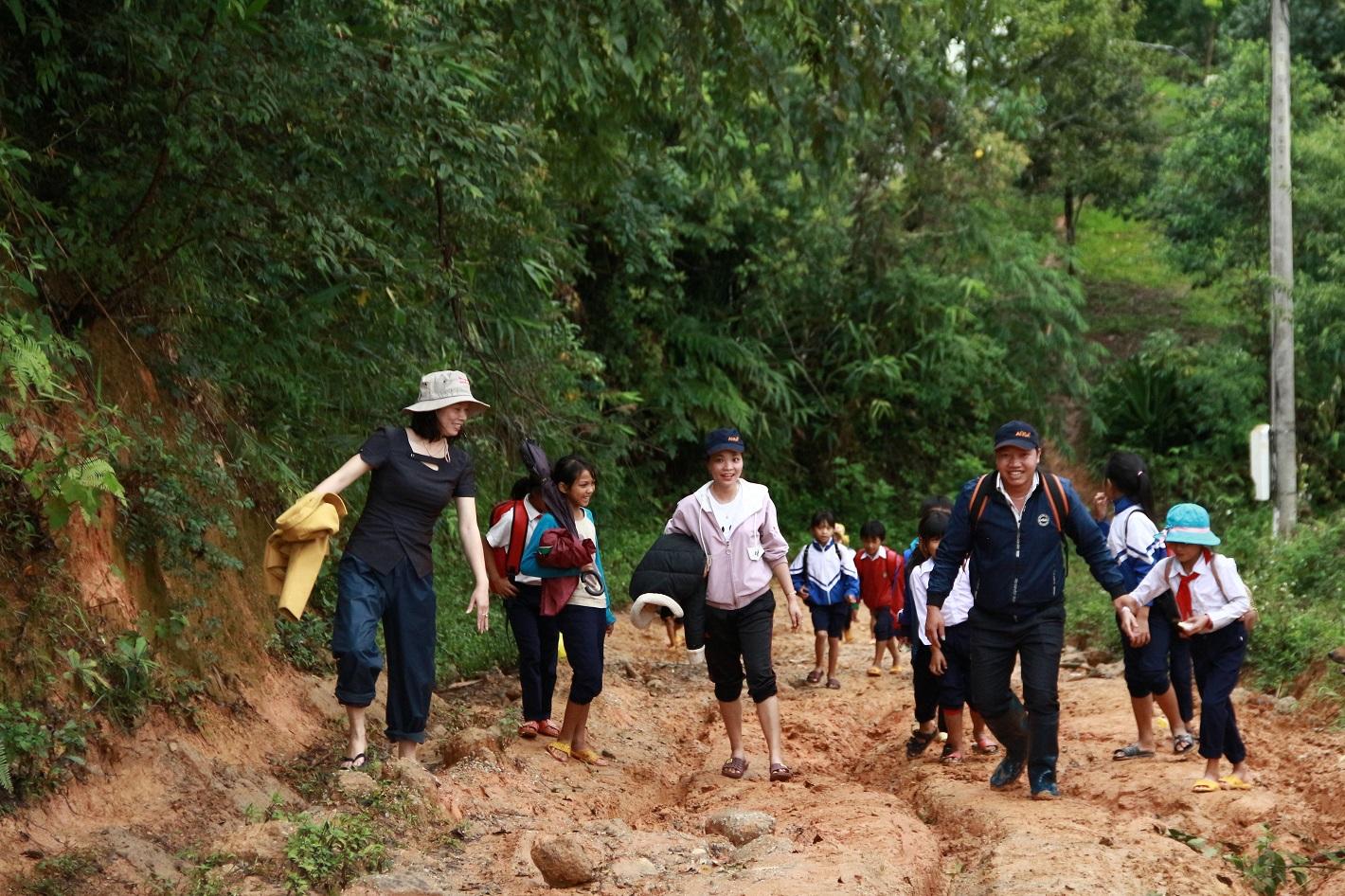 Cô Hồ Thị Thùy Vân (ngoài cùng bên trái), cùng đồng nghiệp vận động đưa học sinh đến lớp. Ảnh: Dung Nguyên.