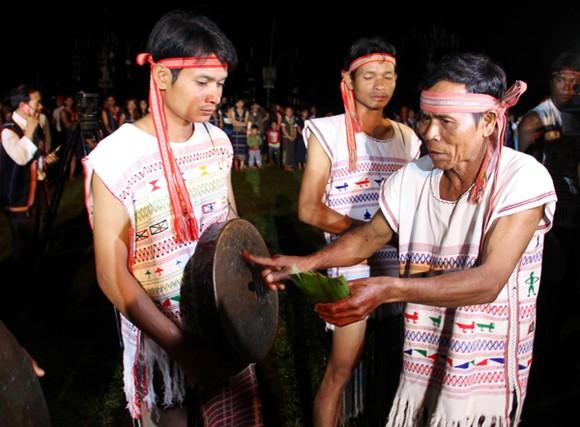 Già làng dân tộc Cơ Ho làm nghi lễ khai chiêng trong đêm hội. Ảnh SGGP