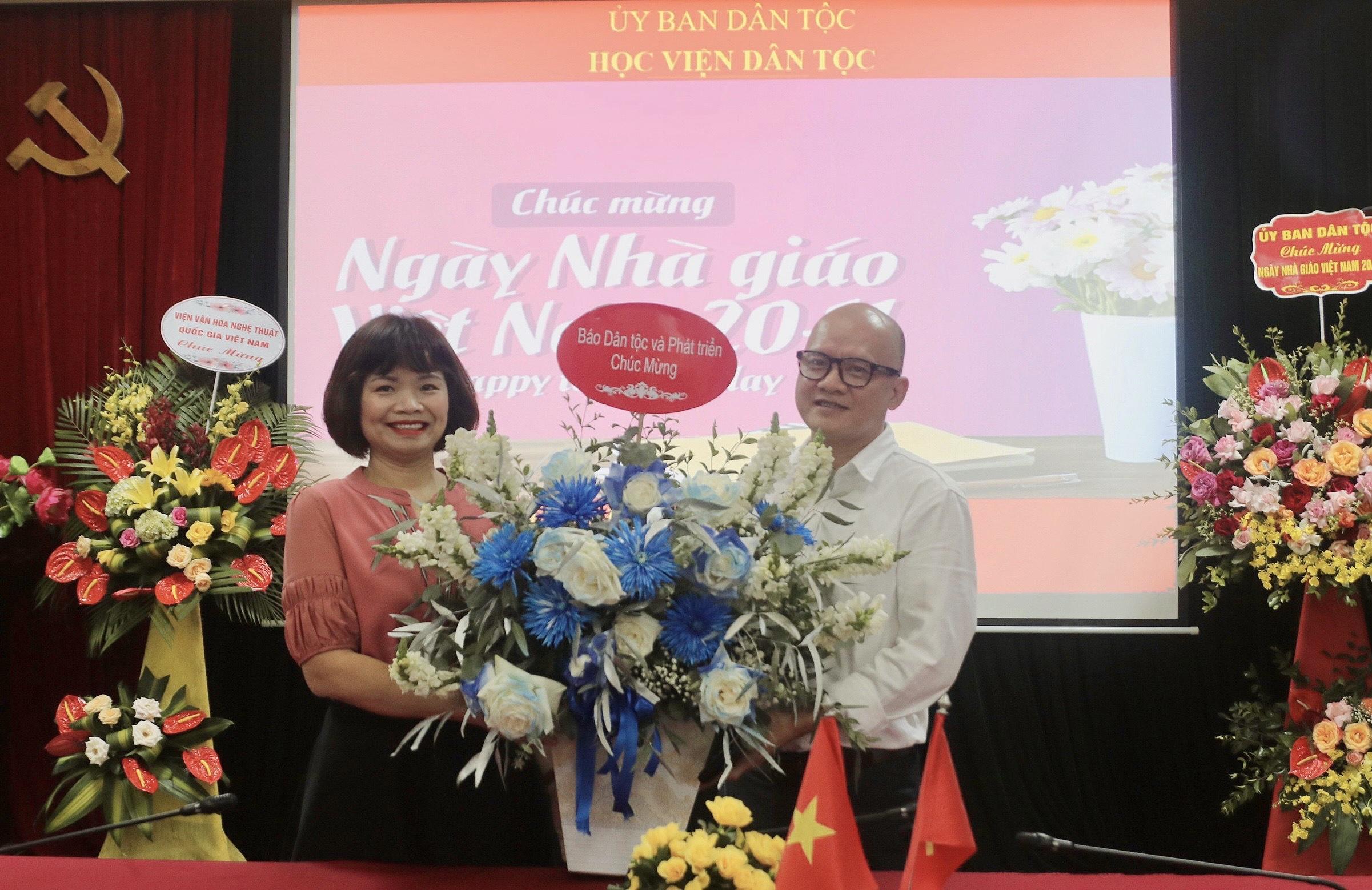 Phó Tổng Biên tập Báo Dân tộc và Phát triển Bùi Thị Hạ tặng hoa chúc mừng Học viện Dân tộc