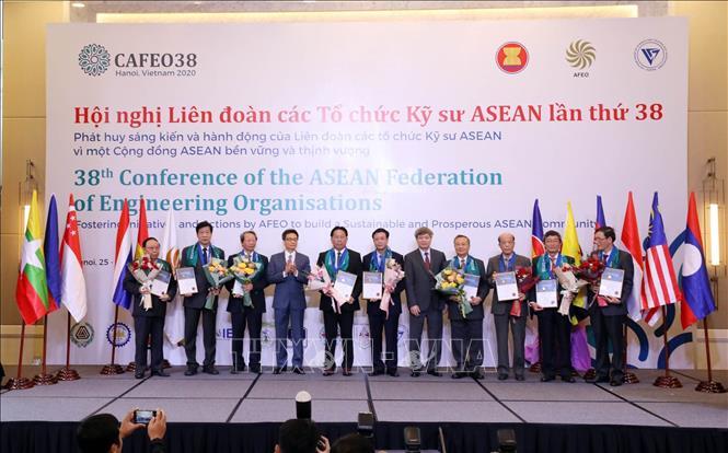 Phó Thủ tướng Chính phủ Vũ Đức Đam và Thứ trưởng Bộ Khoa học và Công nghệ Phạm Công Tạc trao Chứng chỉ Kỹ sư chuyên nghiệp ASEAN và hoa cho các kỹ sư tại Hội nghị. Ảnh: Anh Tuấn/TTXVN