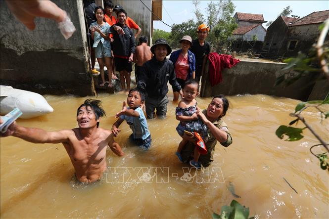 Người dân huyện Lệ Thủy (Quảng Bình) nhận tiền cứu trợ giữa dòng nước lũ, tháng 10/2020. Ảnh: Thành Đạt/TTXVN