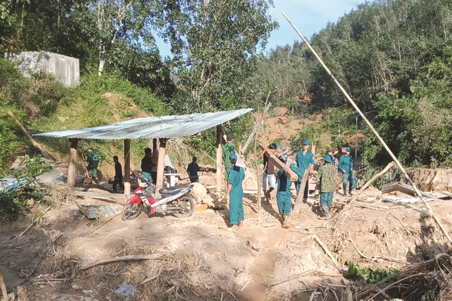Bí thư Chi bộ Phạm Xuân Nghĩa huy động hàng chục dân quân, thanh niên trong làng giúp làm lại nhà ở cho hộ dân bị sập nhà tại làng Tắk Ốc.