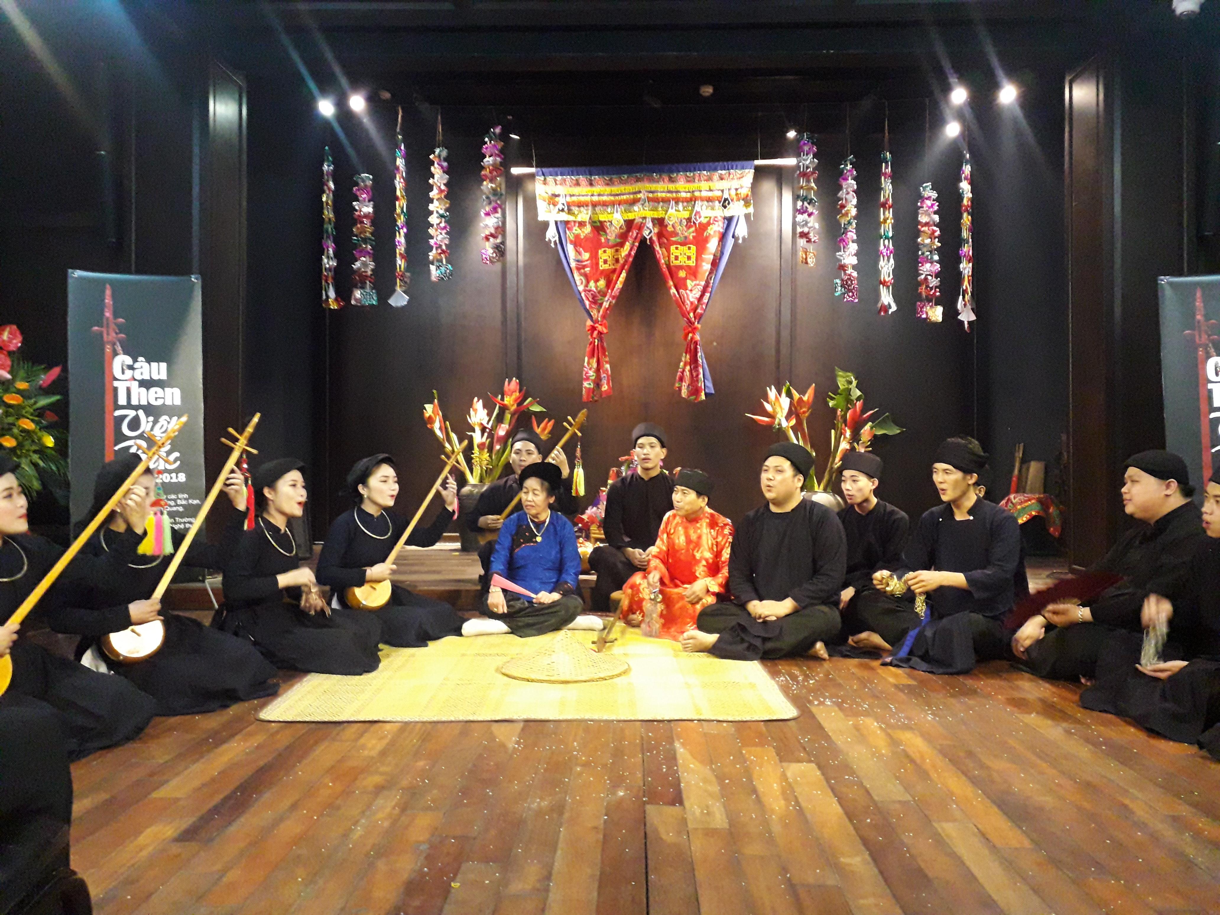 Nghệ nhân Ưu tú Nông Thị Lìm (áo xanh, ngồi giữa) và các để tự thể hiện một trích đoạn Then nghi lễ tại phố cổ- Hà Nội. Ảnh : Ngọc Ánh