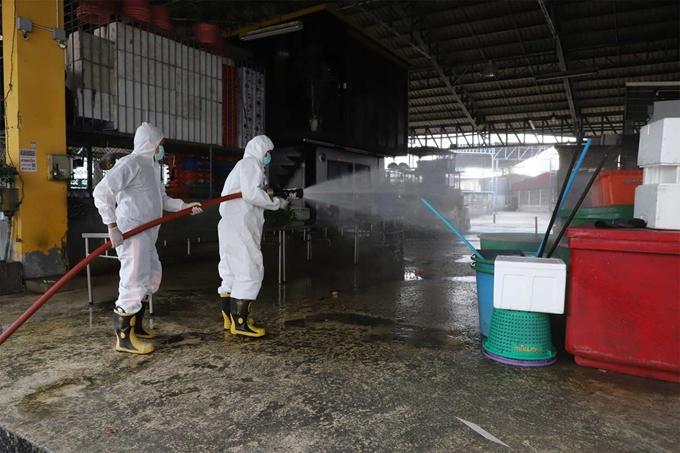 Nhân viên y tế phun thuốc khử trùng tại một cửa hàng thực phẩm ở Samut Sakhon, Thái Lan sau khi chủ cửa hàng bị nhiễm COVID-19 (Ảnh: Bangkok Post)