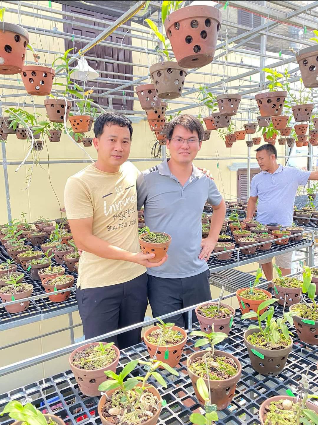 Anh Phạm Thăng Bằng (bên trái) giới thiệu cho khách hàng tham quan vườn lan do anh làm chủ.