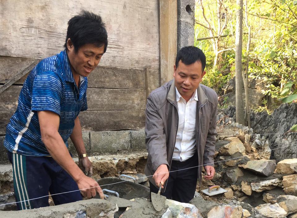 Anh Lý Văn Châư hướng dẫn người dân xóm Nà Sác sửa chữa nhà đón Tết.