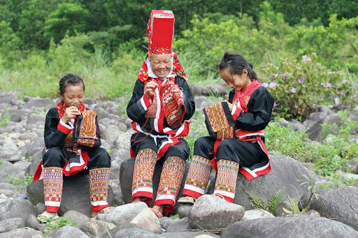 Nghệ nhân Giềng Chống Sếnh hướng dẫn cho thế hệ trẻ cách may trang phục truyền thống người Dao. (Ảnh Việt Hà)
