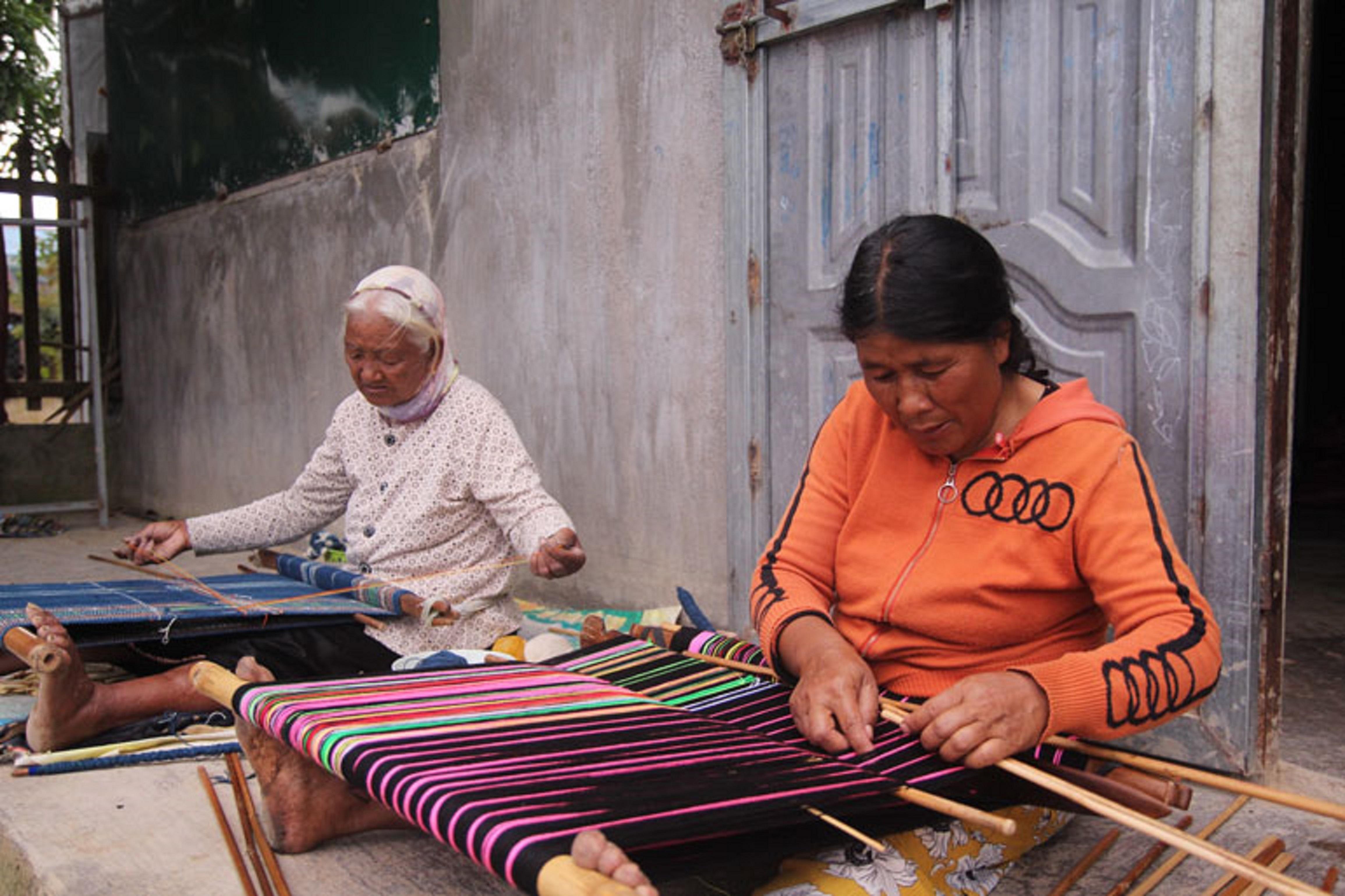 Từ khi thôn Đam Pao được công nhận là làng nghề dệt thổ cẩm truyền thống, gia đình bà K'Jong (áo cam) dệt với số lượng nhiều hơn.