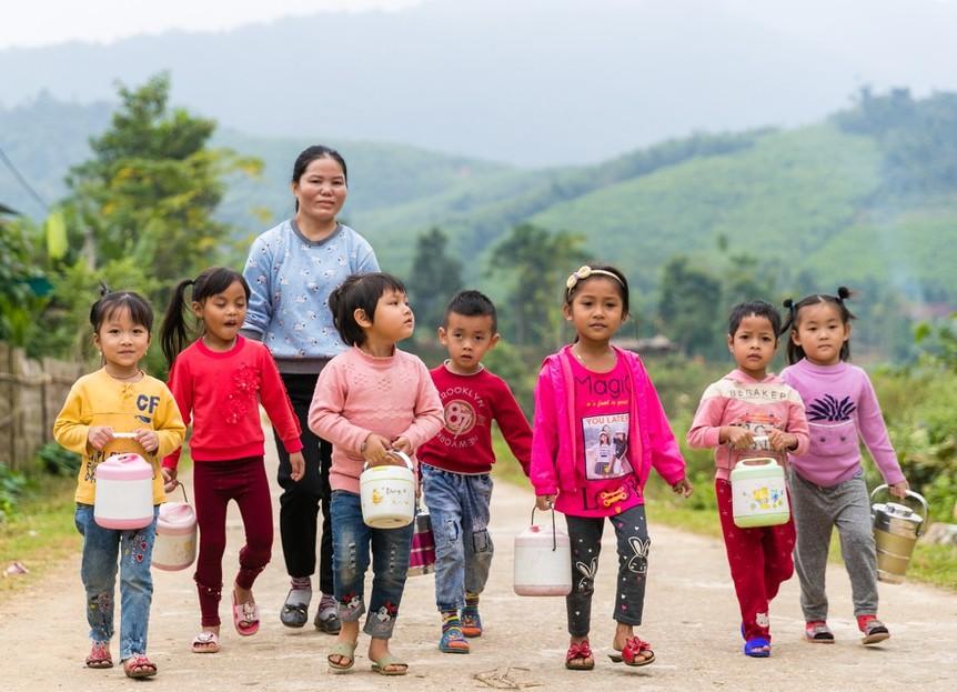 Đám trẻ với những cặp lồng cơm trên tay tung tăng đến trường