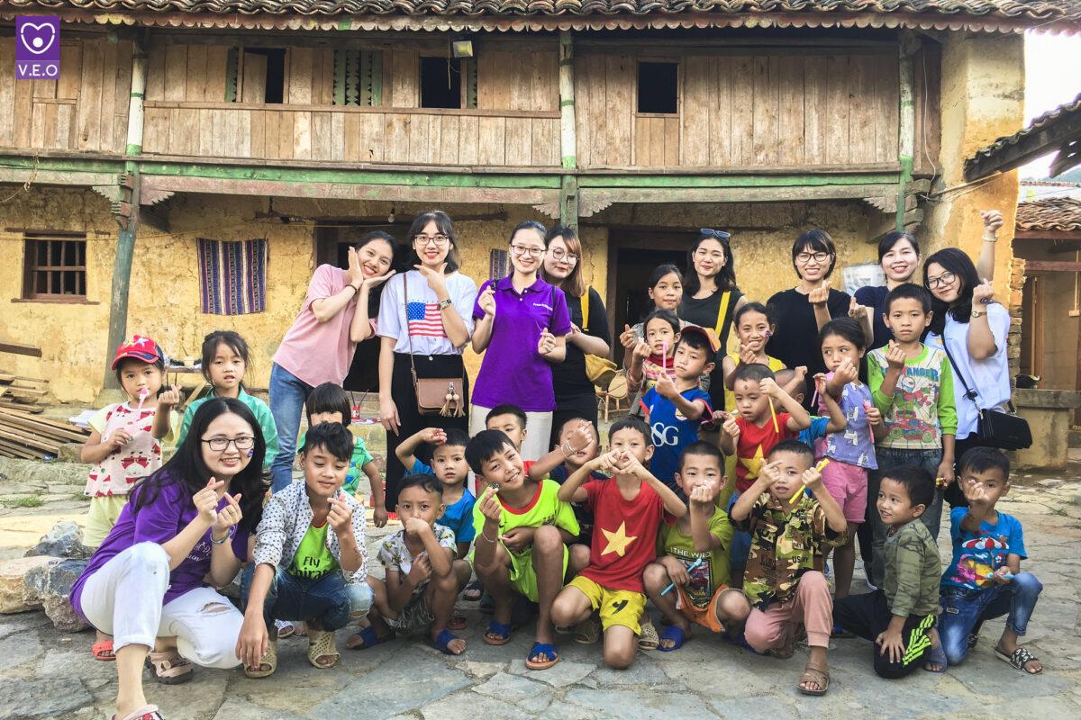 Khách du lịch chụp ảnh với trẻ em vùng cao tại một điểm du lịch cộng đồng ở Hà Giang.