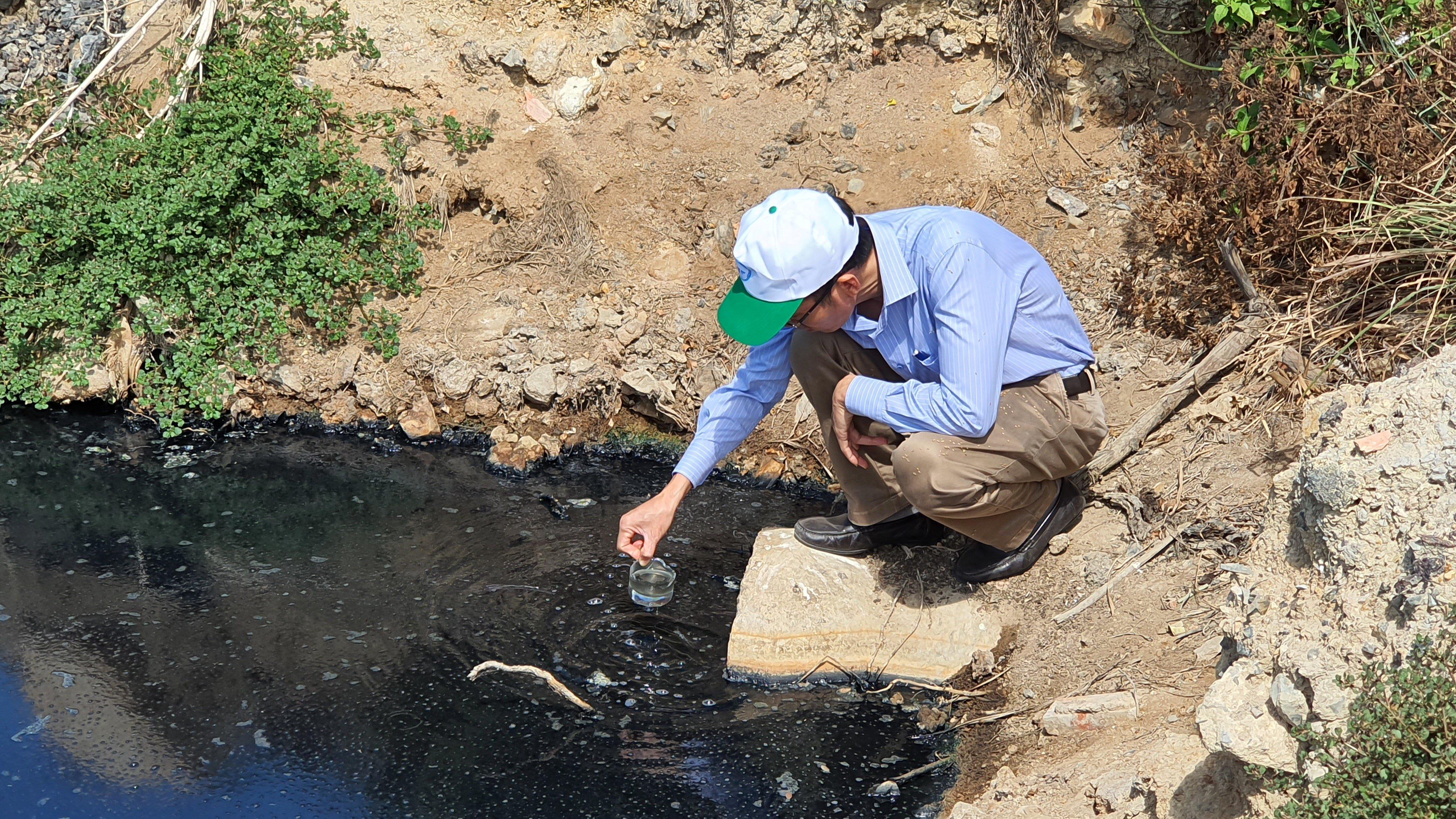 Lực lượng chức năng đang lấy mẫu nước để thử nhiệm tại khu vực cống xả thải.