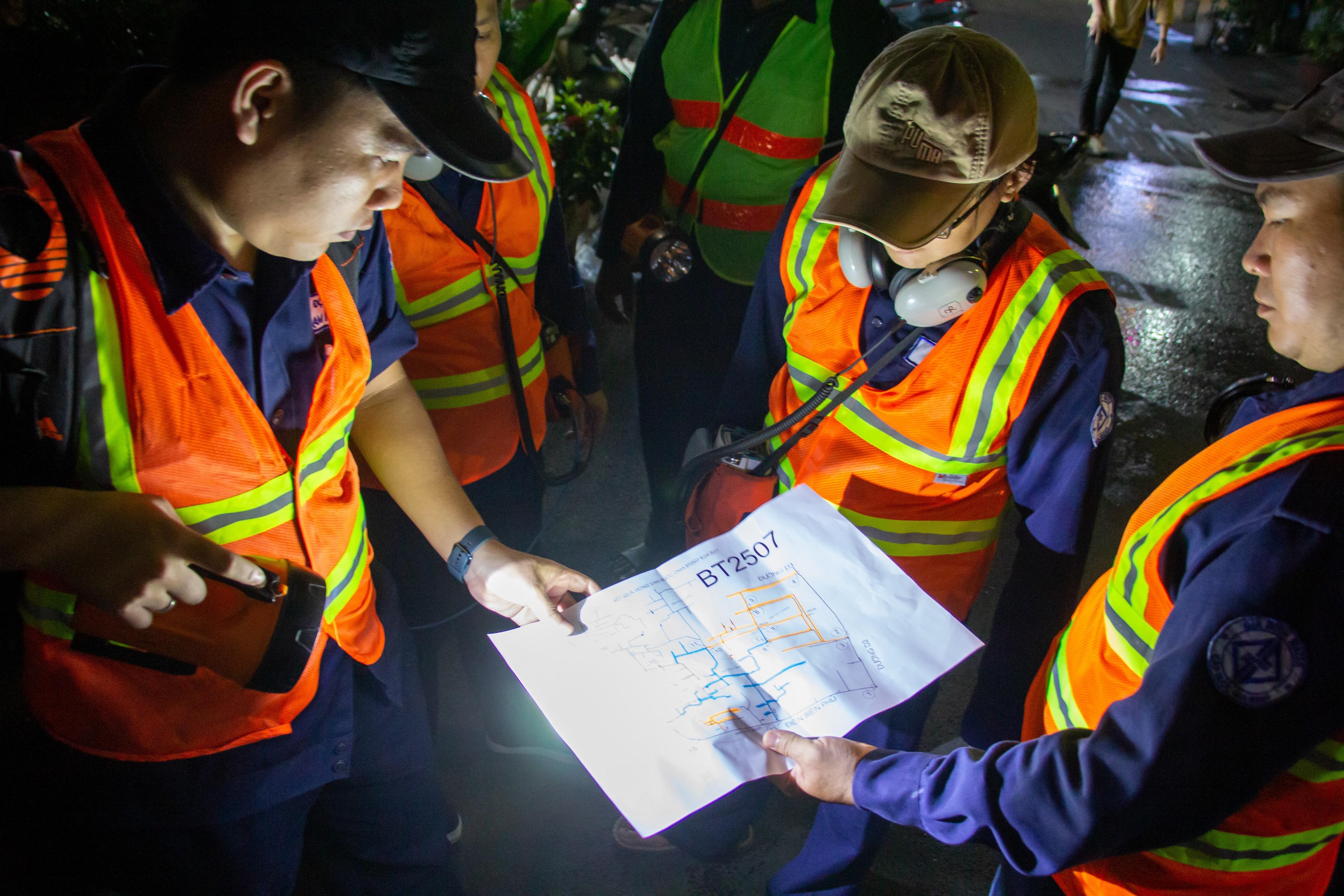 Đội công nhân đi dò đường ống nươc vỡ vào ban đêm tại TP HCM