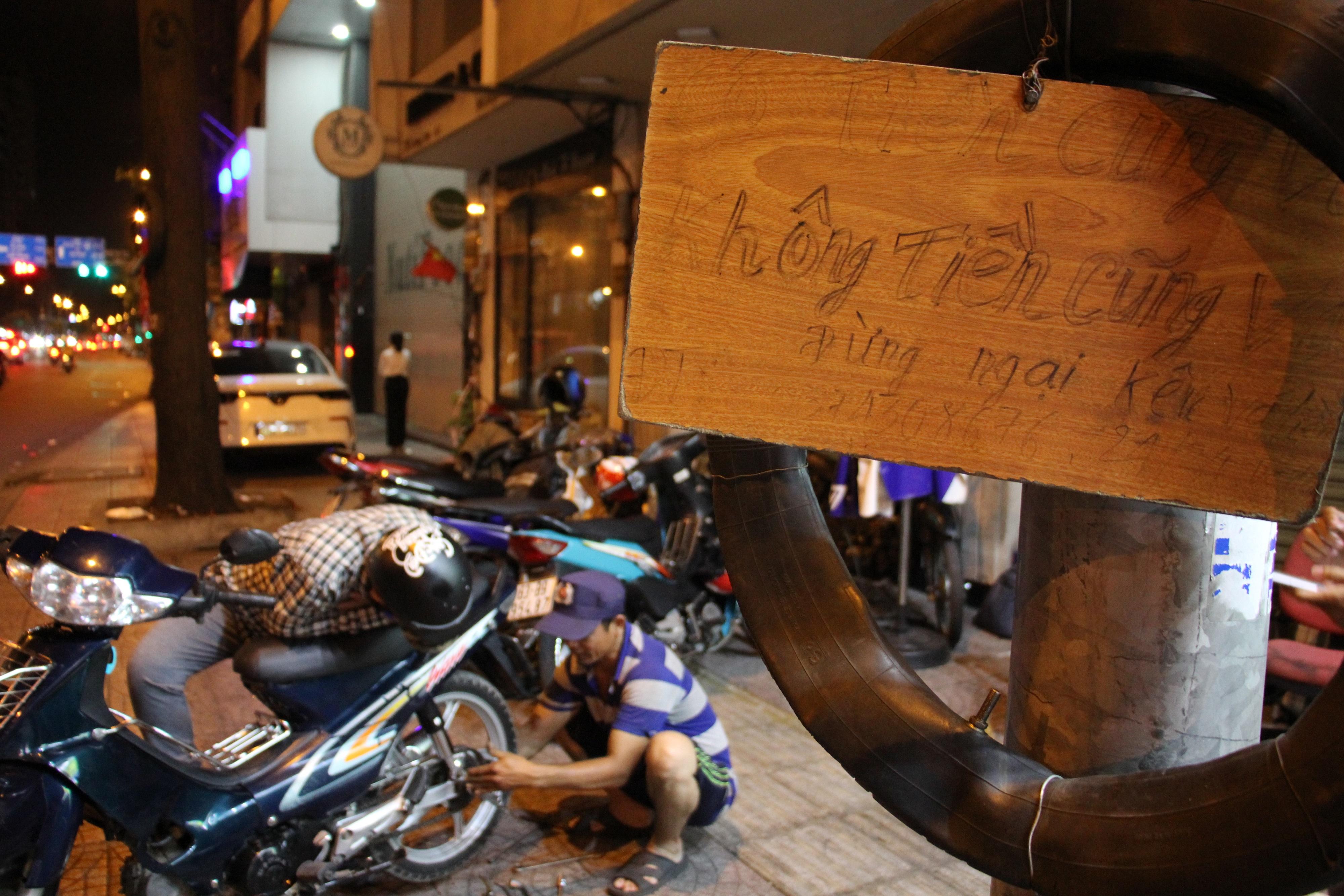 """Anh Nguyễn Văn Hiếu với tấm bảng """"không tiền cũng vá, đừng ngại"""" tại quận 4, TP HCM"""