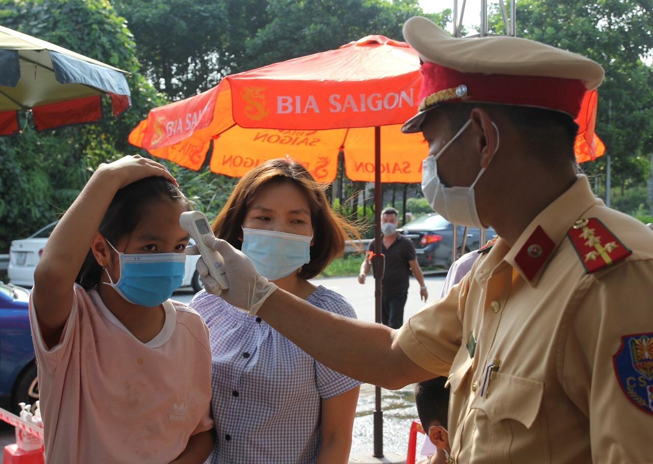 Lực lượng chức năng tiến hành đo thân nhiệt và khai báo y tế cho hành khách qua các chốt kiểm dịch