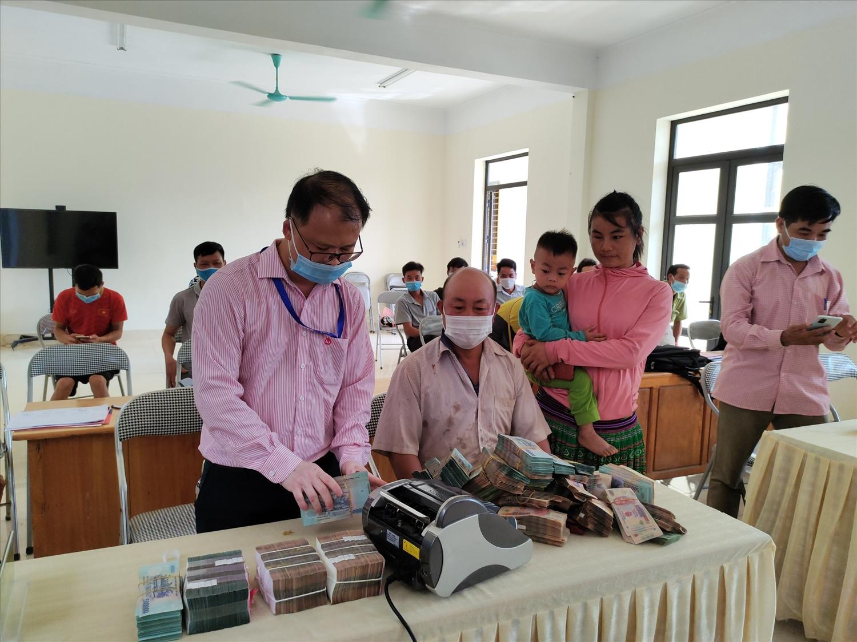 Cán bộ Phòng giao dịch NHCSXH huyện Văn Chấn giúp vợ chồng anh Giàng A Sáu xếp gọn tiền trước khi gửi tiết kiệm.