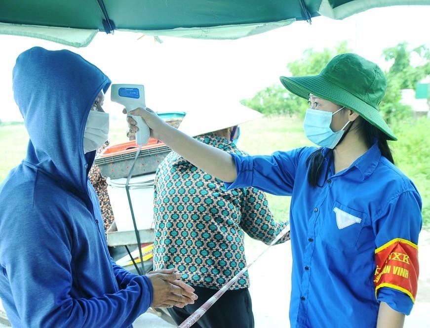 Thanh niên tình nguyện làm nhiệm vụ đo thân nhiệt tại chốt kiểm soát dịch bệnh