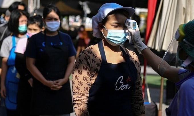 Kiểm tra thân nhiệt tại một khu chợ ở Bangkok, Thái Lan. (Ảnh: Reuters)