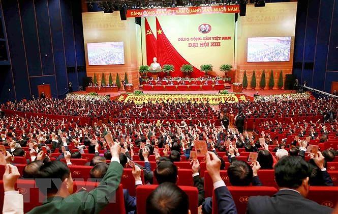 Các đại biểu biểu quyết, thông qua Nghị quyết Đại hội XIII Đảng Cộng sản Việt Nam. (Nguồn: TTXVN)