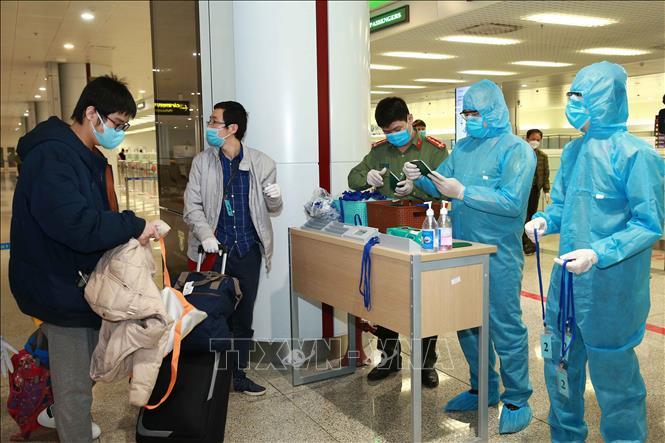Công an cửa khẩu Cảng hàng không Quốc tế Nội Bài kiểm tra hộ chiếu, hướng dẫn và phát thẻ cho hành khách đến khu vực cách ly. Ảnh: Doãn Tấn/TTXVN