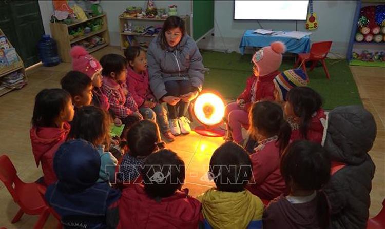 Cô và trò Trường non thôn Cá Ha, xã Giàng Chu Phìn, huyện Mèo Vạc (Hà Giang) sưởi ấm bằng quạt điện. Ảnh: Nguyễn Chiến/TTXVN.