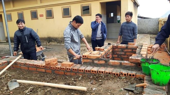 Thầy Quế (thứ 2 từ trái sang) tận tay xây hệ thống ủ nước ấm cho học sinh vùng cao