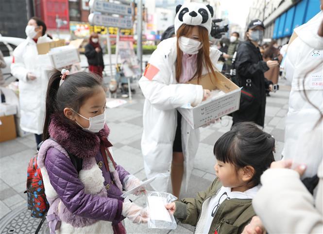 Các tình nguyện viên phát khẩu trang miễn phí cho người dân tại Tokyo, Nhật Bản. Ảnh: THX/TTXVN
