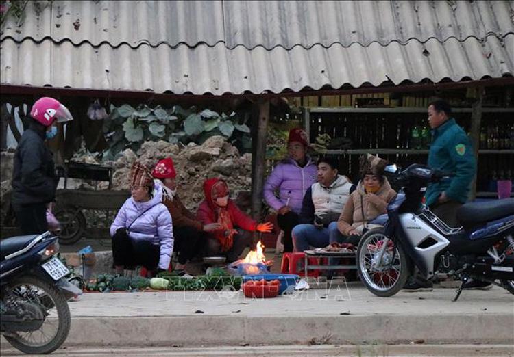 Tại phường Thanh Trường (thành phố Điện Biên Phủ), nhiều tiểu thương tụ tập tại điểm chợ cóc sưởi ấm bên đống lửa. Ảnh: Xuân Tiến-TTXVN
