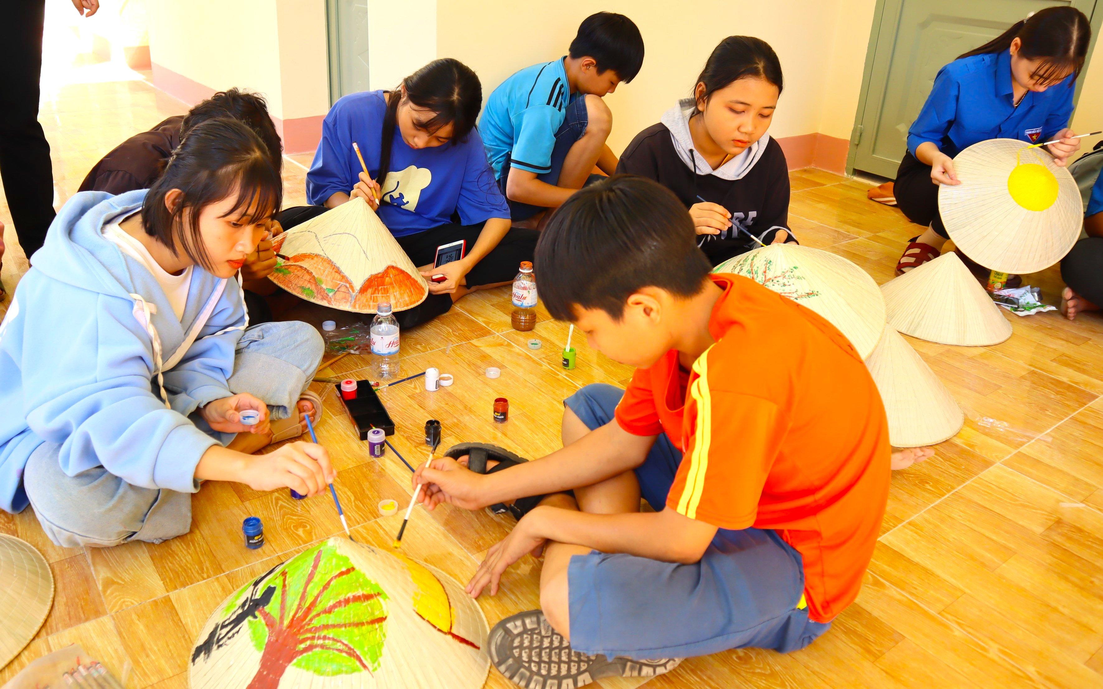 """Sân chơi """"Thiếu nhi với Tết Việt"""", hoạt động vẽ tranh về môi trường trên nón lá và Thư viện lưu động thu hút đối với đoàn viên, thanh thiếu nhi huyện vùng biên"""