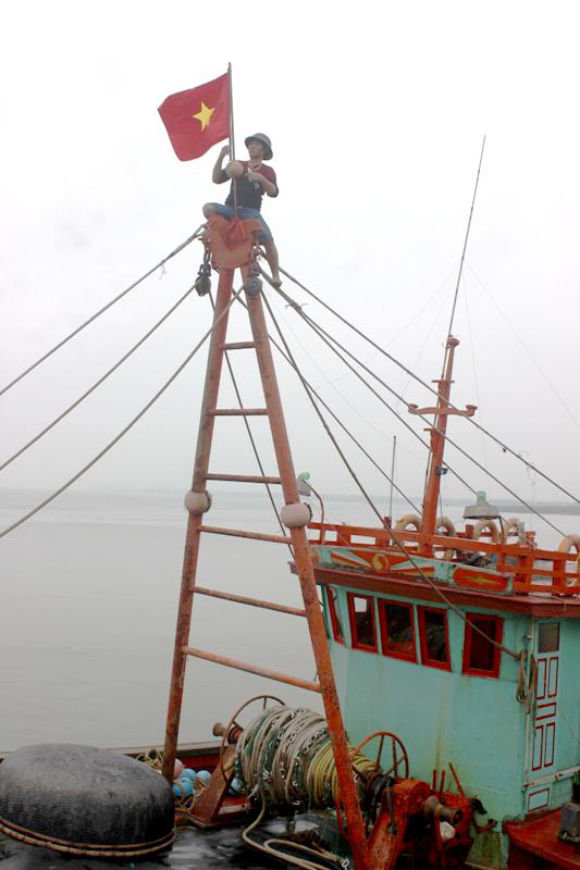 Ngư dân Phạm Văn Tiến treo cờ Tổ quốc trên nóc tàu, chuẩn bị cho chuyến vươn khơi