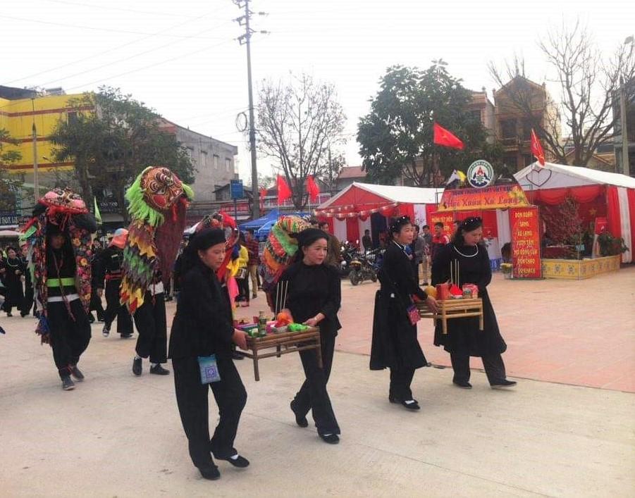 Dân làng bê mâm tế lễ Thần nông trong Lễ hội Lồng tồng, đội ky lằn biểu diễn theo sau