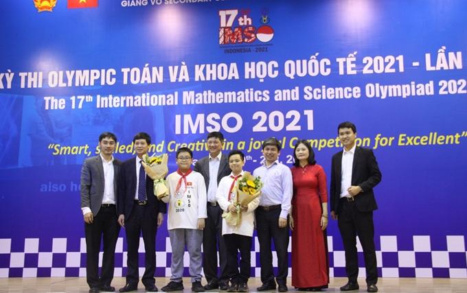Ông Phạm Xuân Tiến, Phó Giám đốc Sở GD&ĐT Hà Nội và lãnh đạo Văn phòng, Phòng Giáo dục Phổ thông (Sở GD&ĐT), Hiệu trưởng Trường THCS Giảng Võ tặng hoa chúc mừng 2 thí sinh Việt Nam giành Huy chương Vàng.