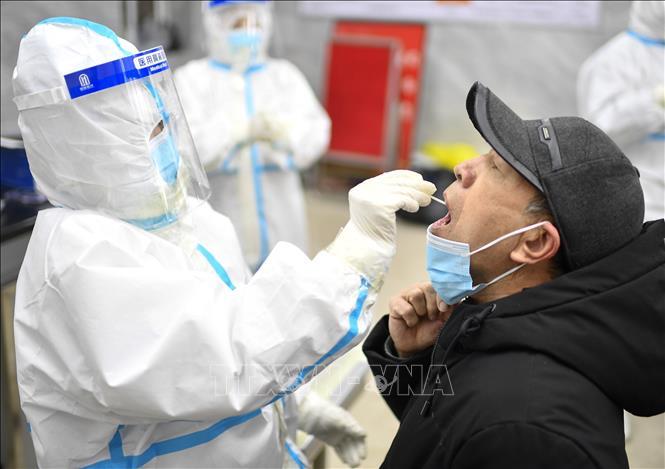 Nhân viên y tế lấy mẫu dịch xét nghiệm COVID-19 cho người dân tại tỉnh Cát Lâm, Trung Quốc, ngày 20/1. Ảnh: THX/TTXVN