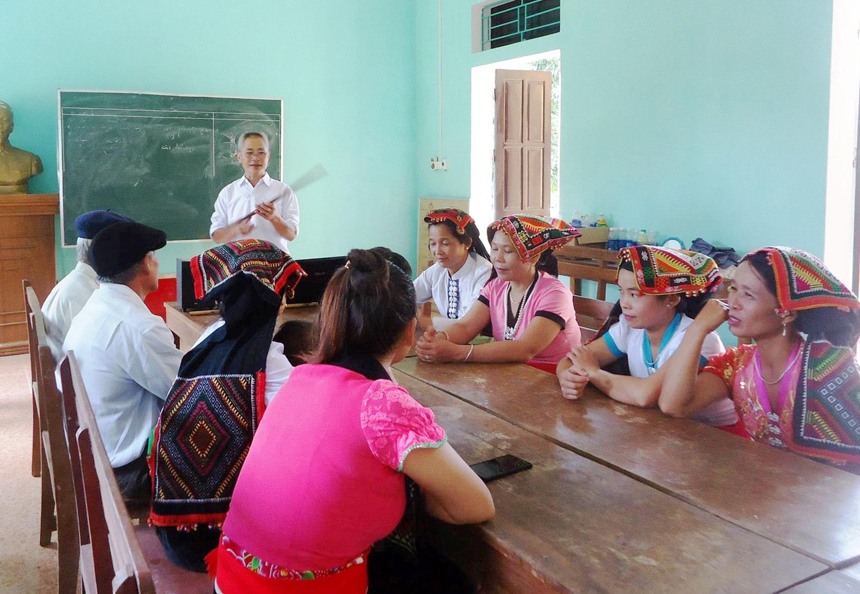 Thầy giáo Lường Đức Chôm đang truyền dạy chữ Thái cổ cho bà con