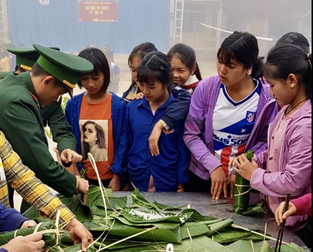 Các chú bộ đội hướng dẫn các cháu học sinh gói bánh chưng