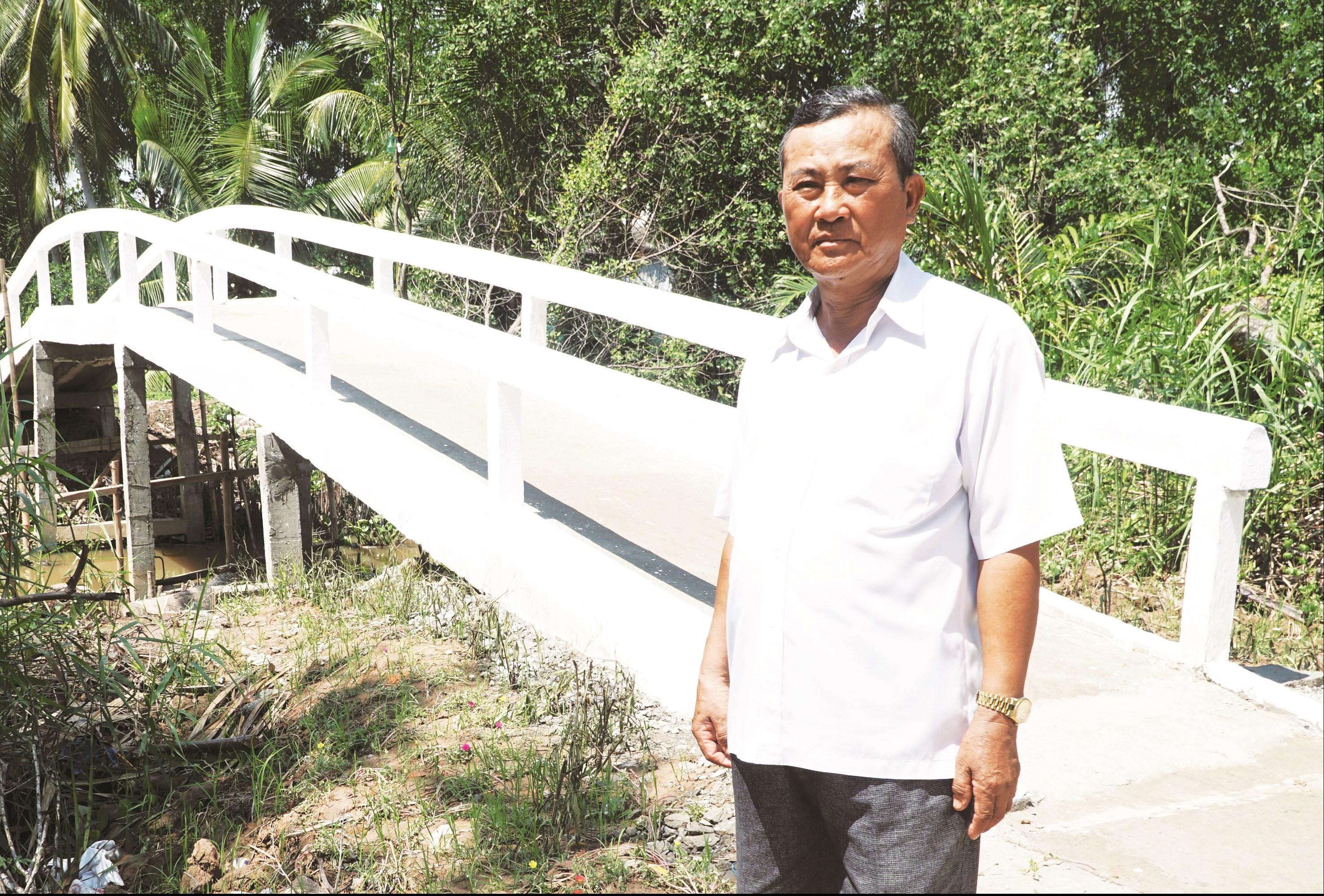 Ông Lâm Văn Phấn bên cây cầu do ông đã đóng góp và huy động để xây mới và sửa chữa.