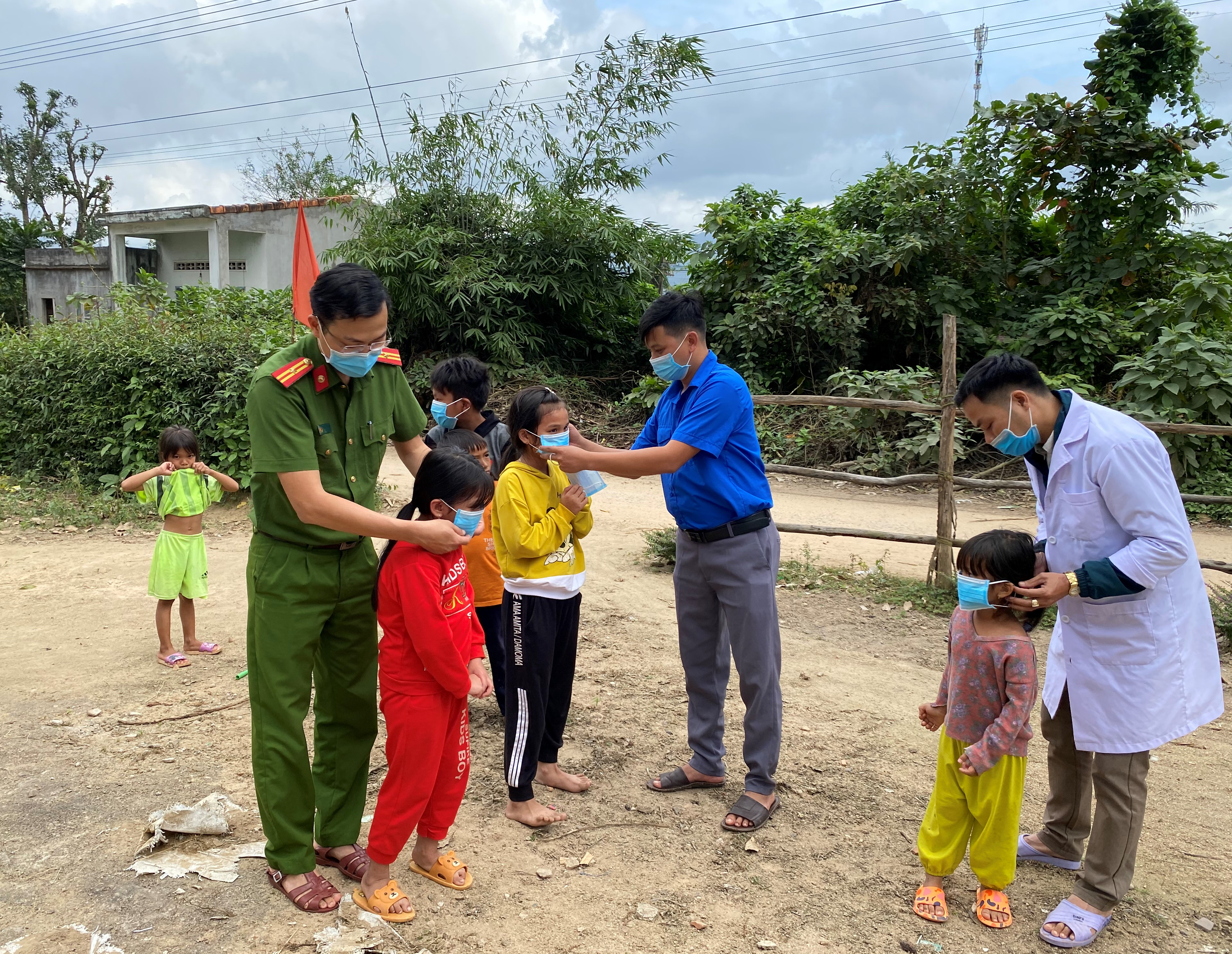 Đoàn viên, thanh niên xã Canh Hiệp phối hợp với cán bộ y tế và Công an xã hướng dẫn trẻ em đeo khẩu trang tại khu dân cư làng Hiệp Hưng.