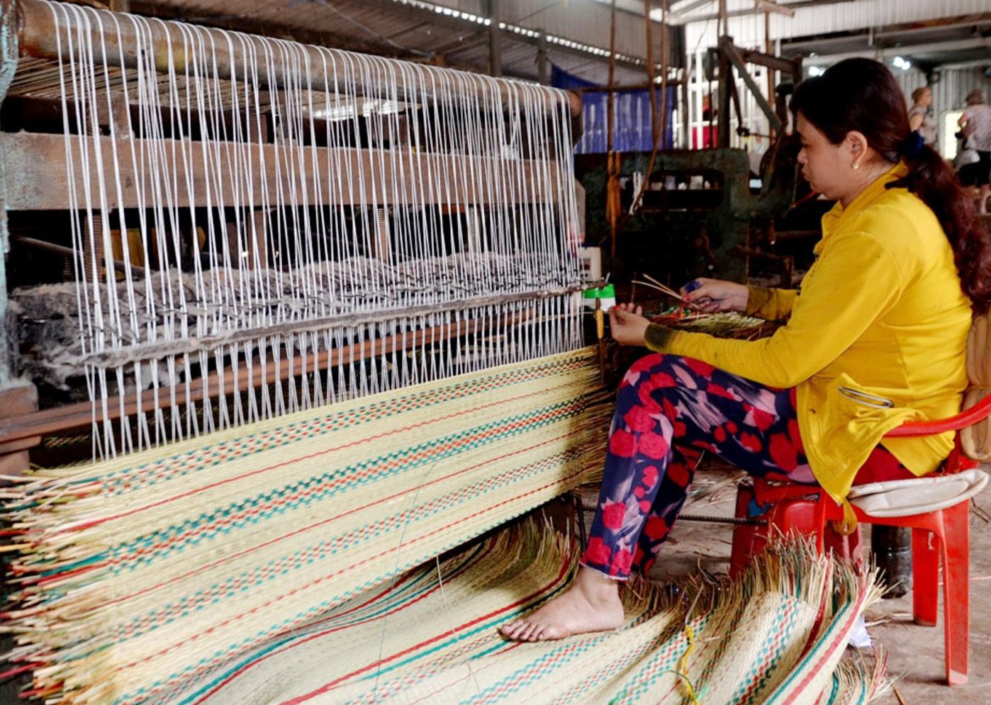 Chị Nguyễn Xuân Mỹ, ở phường Long Châu có thu nhập ổn định nhờ nghề dệt chiếu Uzu.