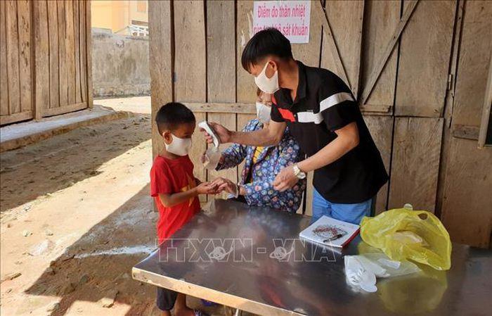 Học sinh Trường Tiểu học xã Tá Pạ, huyện Mường Tè (Lai Châu) được giáo viên đo thân nhiệt. Ảnh tư liệu: Việt Hoàng/TTXVN