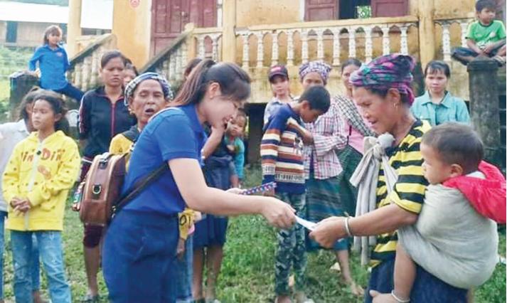Cao Thị Giang (áo xanh) tặng quà cho đồng bào DTTS.