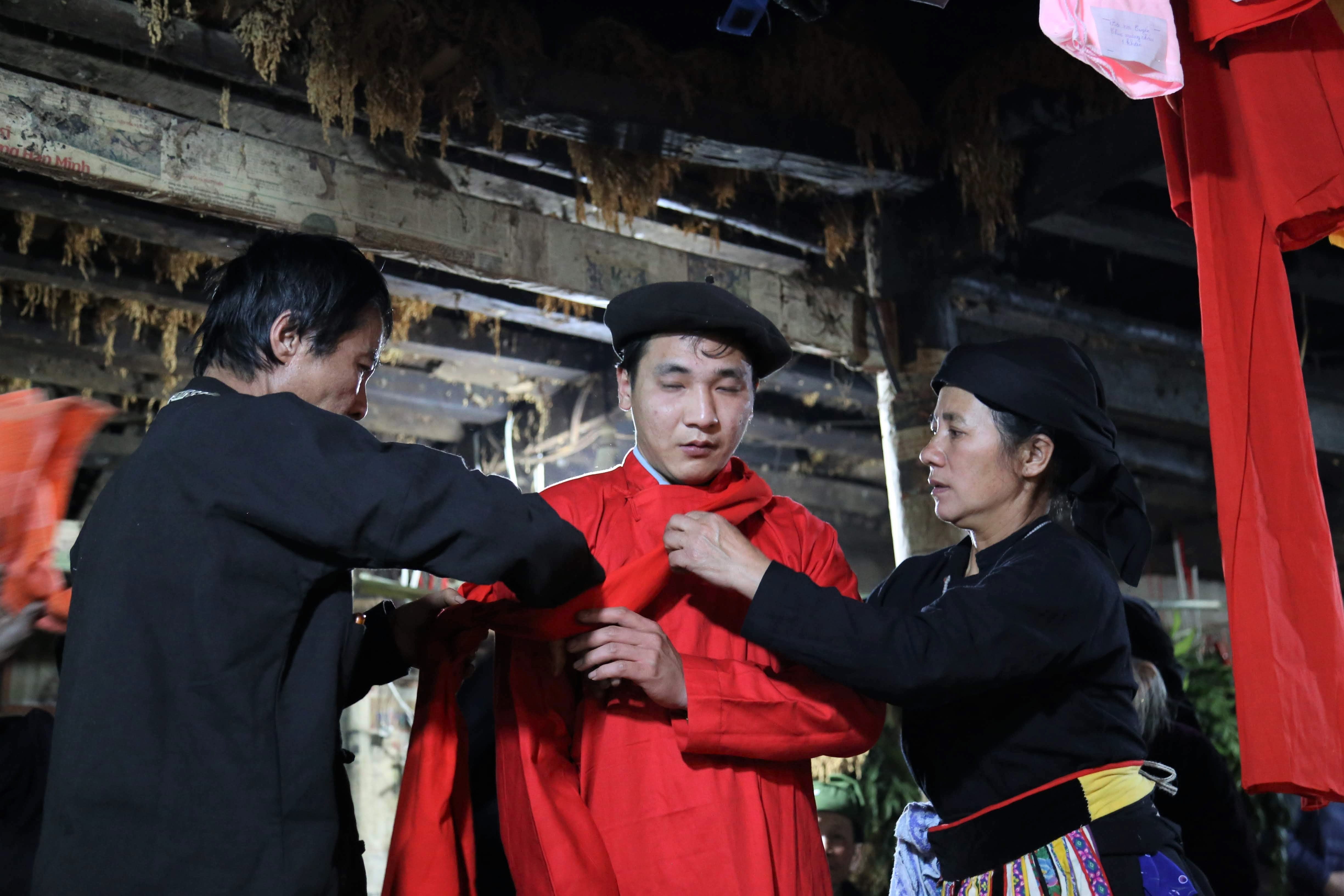 Bố mẹ mặc trang phục màu đỏ cho thầy tào sau khi làm lễ tẩy rửa những điều không tốt.