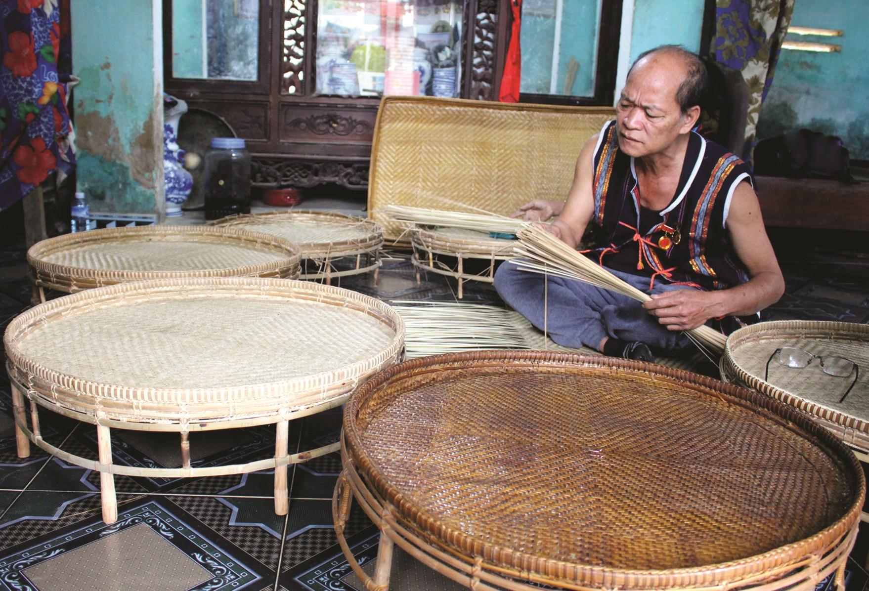 Già làng uy tín Alăng Phương đang đan mâm mây giữ nghề đan đát truyền thống của người Cơ Tu.