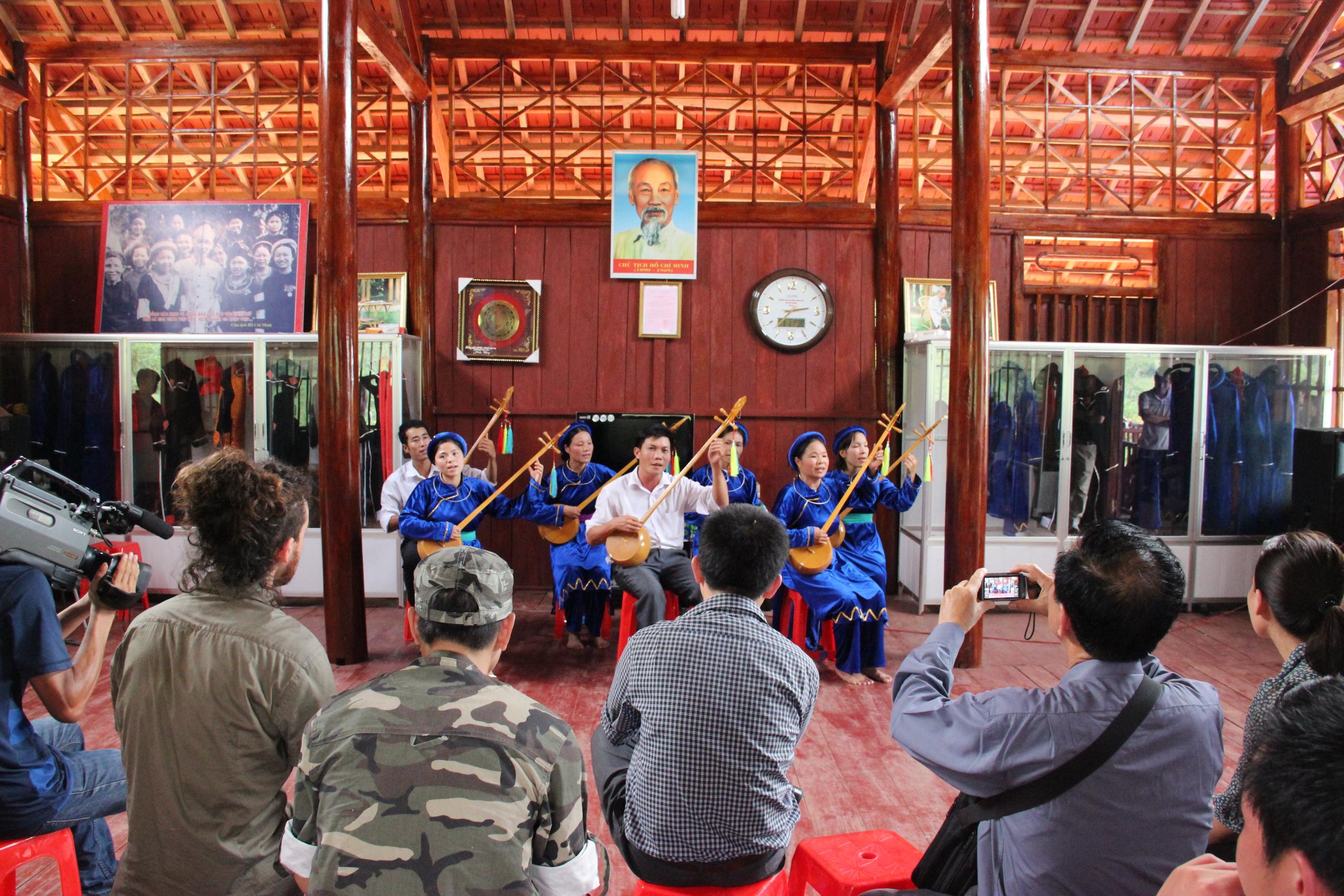 Khách nước ngoài xem biểu diễn hát then, đàn tính tại điểm DLCĐ thôn Nà Ó, xã An Lạc, huyện Sơn Động