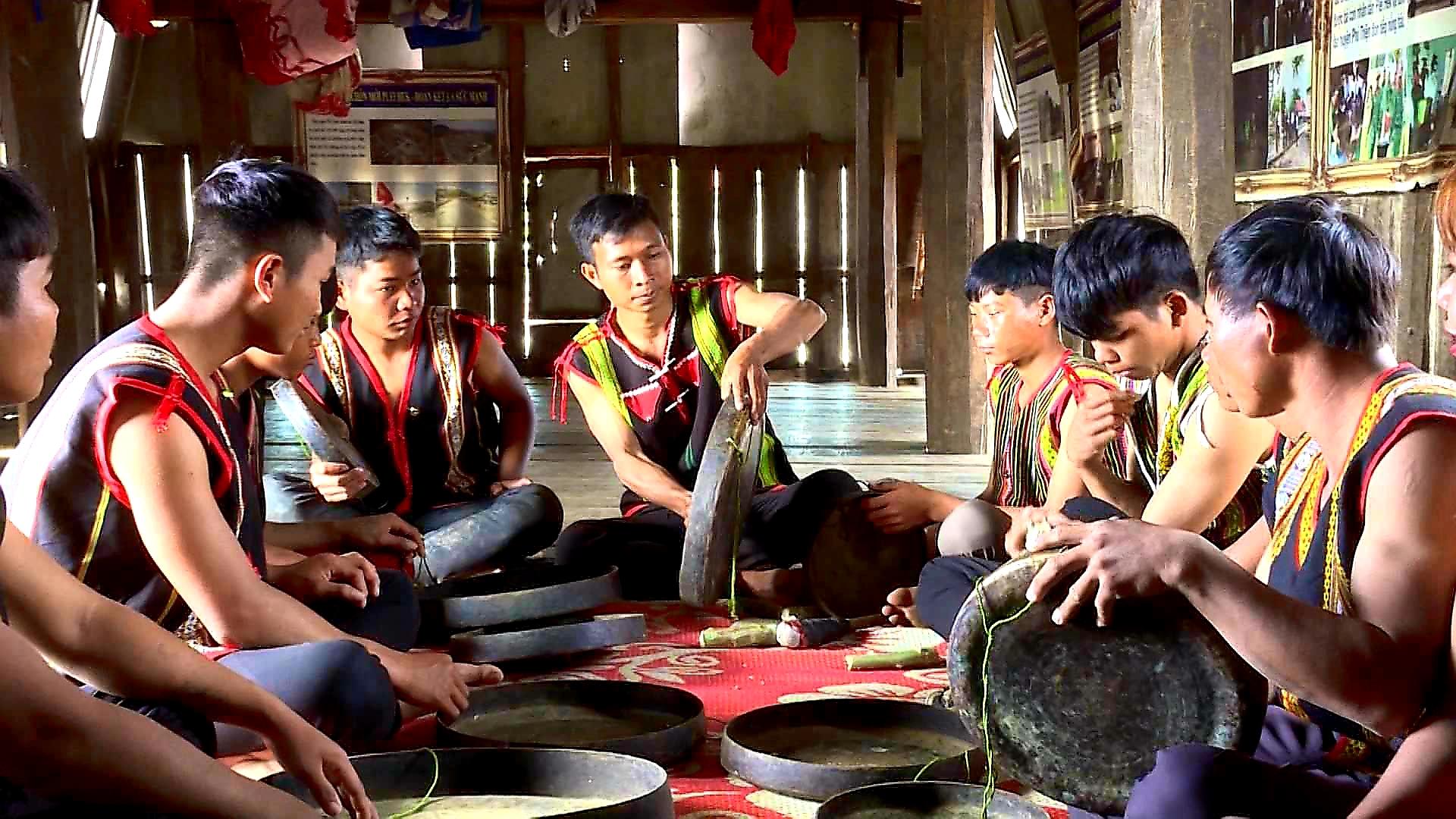 Rmah Mich (ở giữa) đang truyền dạy cồng chiêng cho lớp trẻ trong làng tại nhà rông