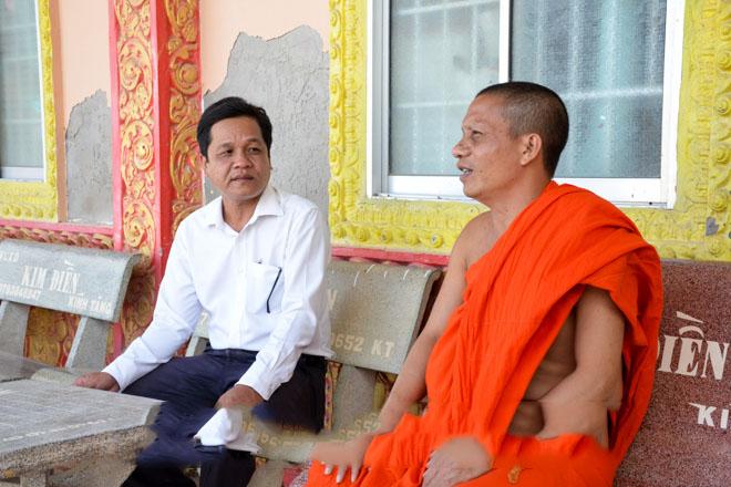 Đại đức Lâm Hữu Tài (người bên phải) trao đổi công việc với lãnh đạo Ủy ban Mặt trận Tổ quốc Việt Nam xã Lịch Hội Thượng (huyện Trần Đề). Ảnh: H.LAN