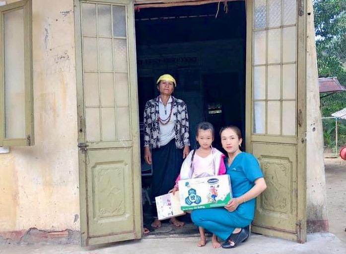 Chị Phan Thị Ánh Ly tặng quà của các nhà hảo tâm cho cháu Kim Na (thôn Gò Chè, xã Long Sơn) bị bệnh viêm màng não