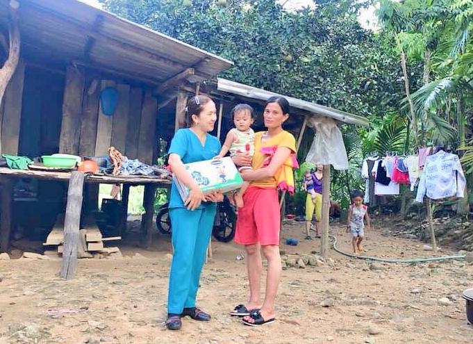 Chị Phan Thị Ánh Ly tặng quà của các nhà hảo tâm cho cháu Đinh Thị Mận, thôn An Thanh, xã Thanh An, huyện Minh Long